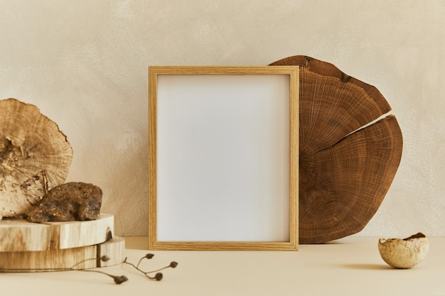 Composition of cozy minimalistic interior design with mock up poster frame, natural materials as wood and marbel, dry plants and personal accessories. neutral beige colors, template.