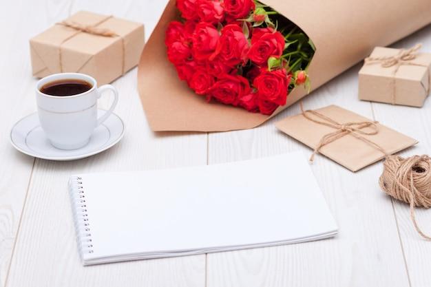 組成。一杯のコーヒー、赤いバラ、ギフトボックス、ノート。天然素材のコンセプト。