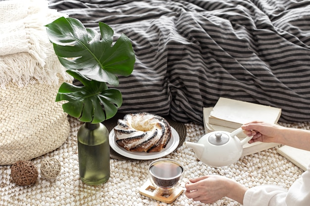 Composition of a cup of tea, homemade cupcake and decorative leaves in a vase against the background of a cozy bed.