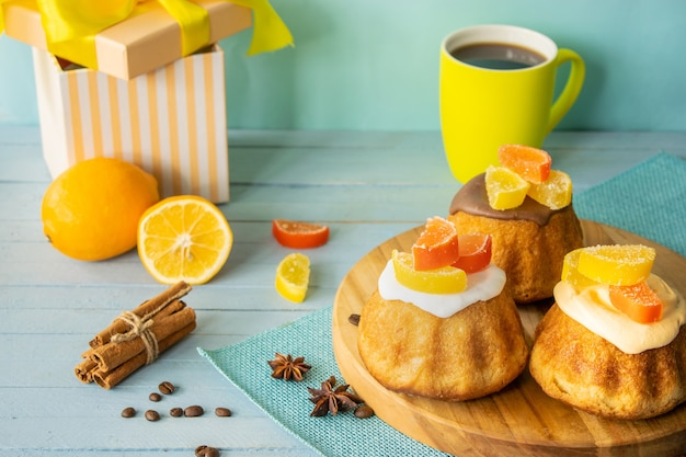 Composition cupcakes with icing imarmelade cup of coffee on a wooden background