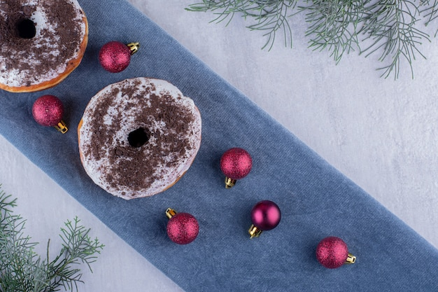 Composition of delicious donuts and christmas decorations on a folded tablecloth on white background.