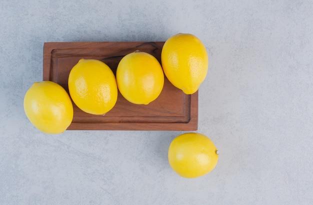 Composizione di deliziosi limoni su tavola di legno.