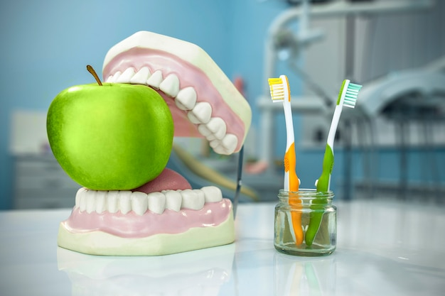 Composition. denture, apple and toothbrushes in glass in dental surgery