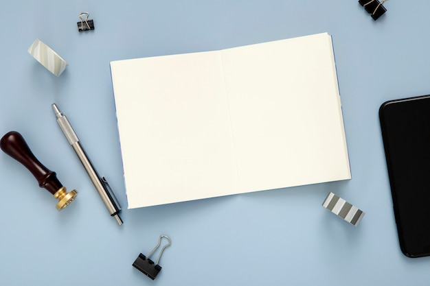 Composition of desk elements on blue background with opened empty notebook