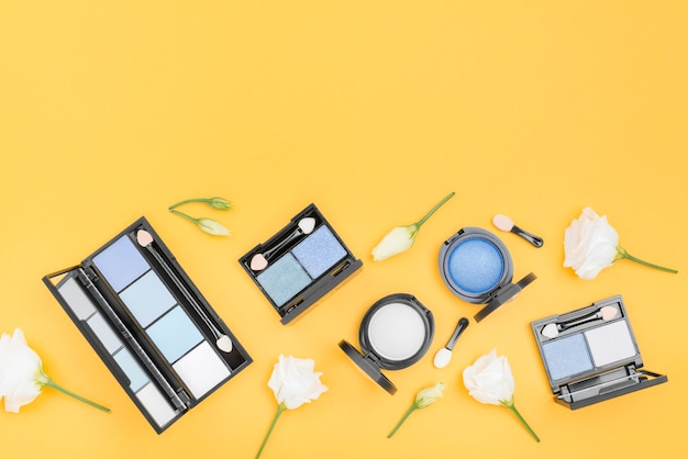 Composition of different cosmetics with copy space on yellow background