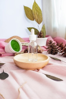 The composition displays the product. transparent skincare bottle with natural dry leaves background. minimalist composition featuring products