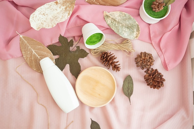 The composition displays the product. white cosmetic bottle with natural dried leaves decoration. minimalist composition featuring products
