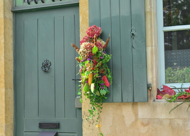 A composition of dried flowers hydrangeas, ivy, cane corn and berries hanging on a vintage door