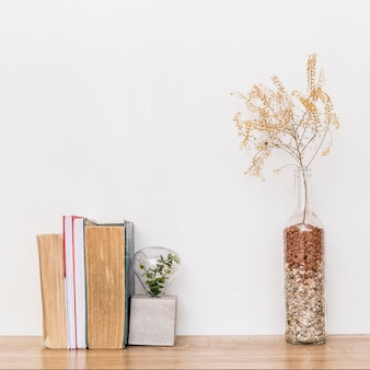 Composition of dried plants and books on table