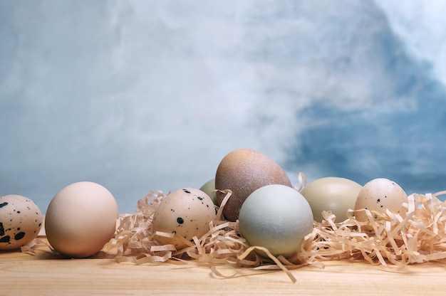 Composition of eggs and feathers on a blue watercolor background.