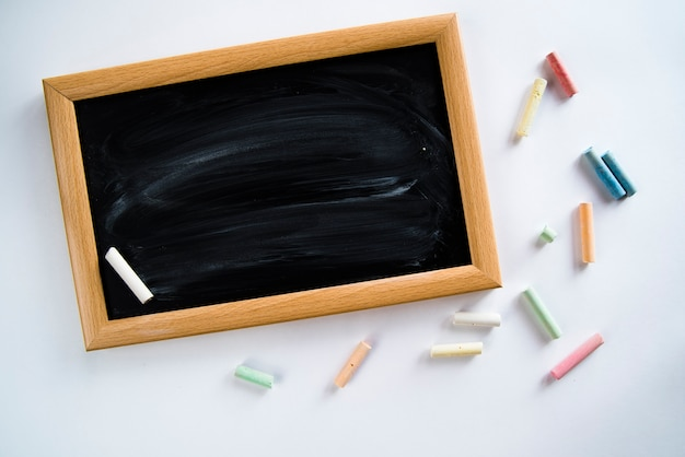 Composition of empty blackboard and colorful chalks