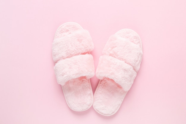 Composition of faux fur slippers on light pink