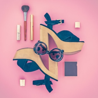 Composition of female accessories and shoes on a pink background