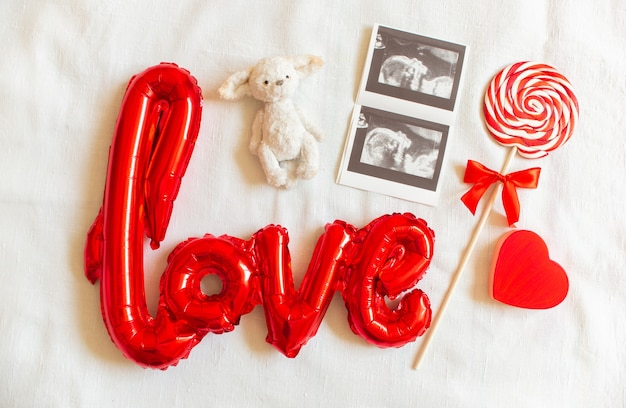 Composition flat lay with baby accessories on white bed background. ultrasound, lollipop, toy bear, heart.