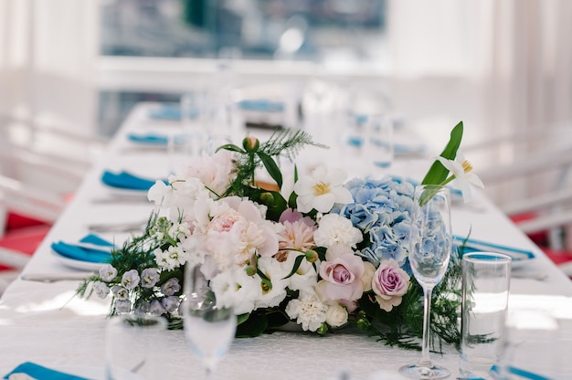 A composition of flowers and greenery is on a festive table at the wedding party. close up.