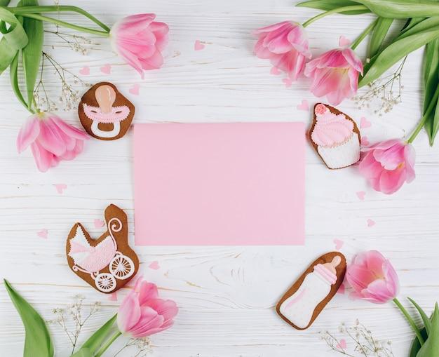 ピンクのチューリップ、ハート、クッキーを持つ木製の背景に新生児のための組成物