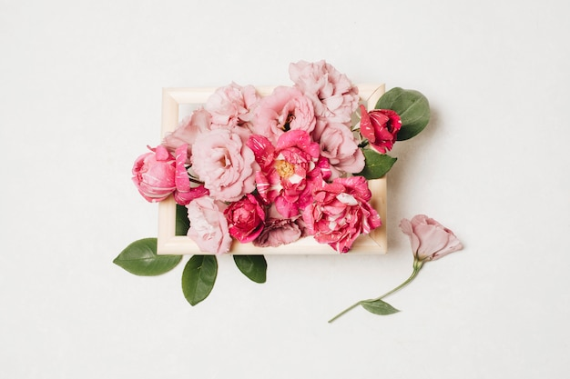 Composition of fresh beautiful pink flowers in box near leaves