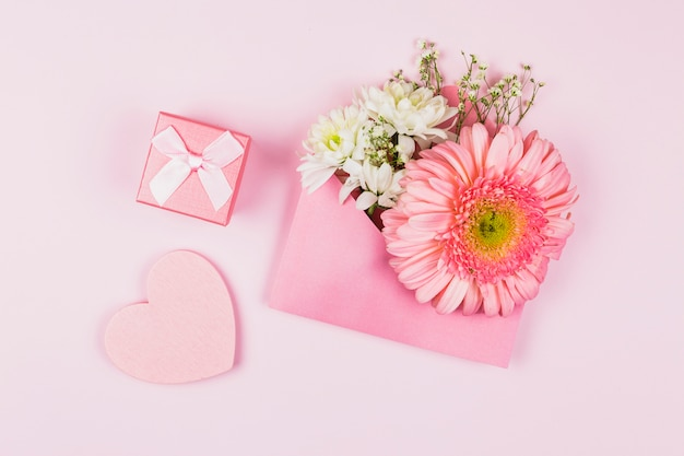 Composition of fresh flowers in envelope near present and ornamental heart