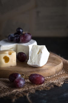 Composition of fresh grapes with cheese on a wooden table.