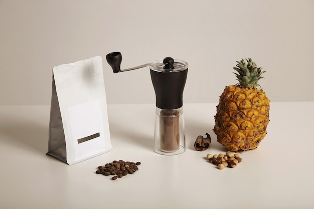 A composition of freshly ground coffee in a manual grinder, bag of coffee beans, nuts, cinnamonnd pineapple on white
