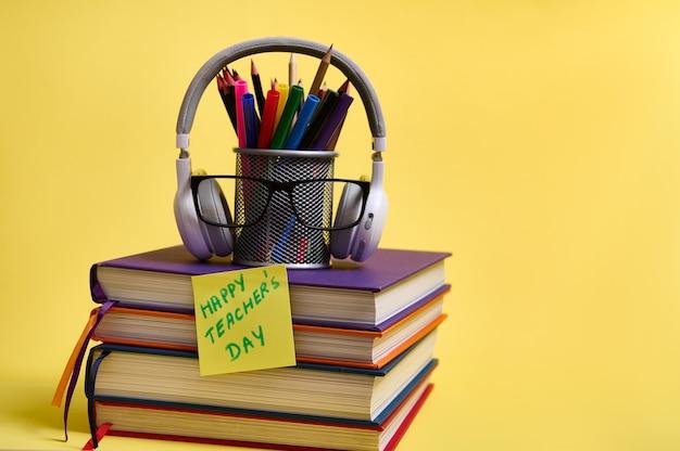 Композиция из стопки красочных книг, карандаши, очки, беспроводные наушники, бумага для заметок с надписью день учителя на желтом фоне с копией пространства. вернемся к школьным концепциям.