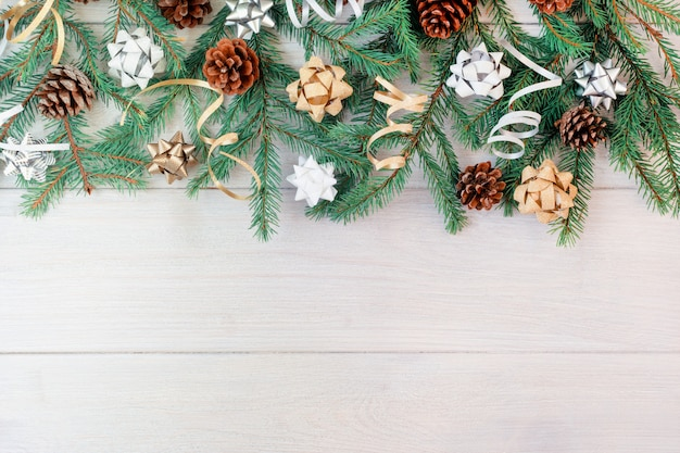 Composition from branches of a christmas tree, cones, decorative ribbons and bows.