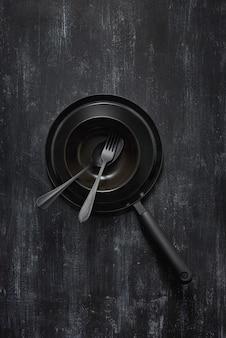 同じ色の石の背景で新鮮で健康的な自然食品を調理および調理するための空の黒いキッチン設備からの構成。上面図。