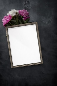 Композиция из цветов. белая фоторамка и розовые и белые пионы. плоская планировка, вид сверху.