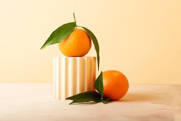 Композиция из свежих мандаринов и геометрического подиума. современный натюрморт. символ нового года. бежевые нейтральные цвета.