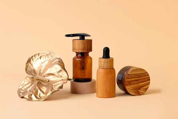 Composition from the wooden cosmetics bottles and golden flamingo flowerneutral beige colors