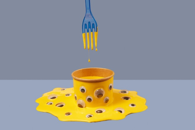 Composition from yellow paint can with plastic googly eyes in the puddle of this paint, blue plastic fork above and droplets of this liquid on a duotone background, copy space.
