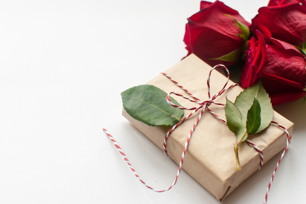 Composition of gift and bouquet of red roses on white background