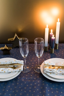 Composition of glasses, plates and cutlery near burning candles