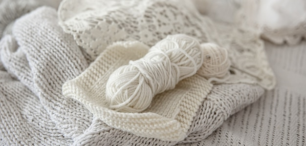 Composition of handmade knitted products and threads in pastel colors.