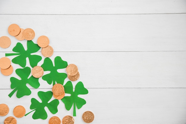 Composition of heap of coins and green paper clovers on board