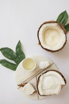 Composition of herbal coconut cosmetic products with blank card and green leaves on white surface