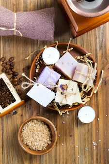 Composition of homemade coffee soap, sea salt in a bowl and coffee beans on a brown wooden table.