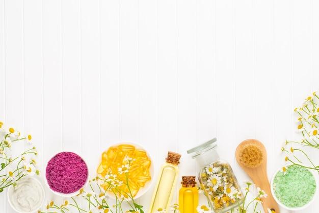 自家製化粧品、自然化粧品と明るい背景のカモミールの花によるアロマテラピーを構成します。