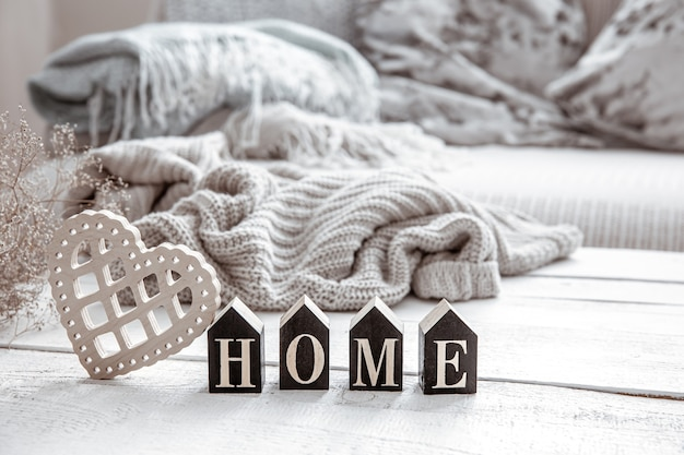 Composition in hygge style with wooden word home, heart and knitted element