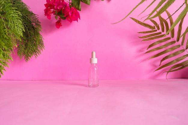 製品をフィーチャーした構成アイデアのコンセプト。 、乾燥した葉、松の葉、赤い花で飾られたピンクの背景に化粧品ボトル