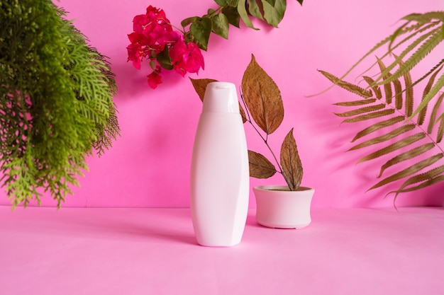 Composition ideas concept featuring products. cosmetic bottles on pink background decorated with , dried leaves, pine leaves and red flowers