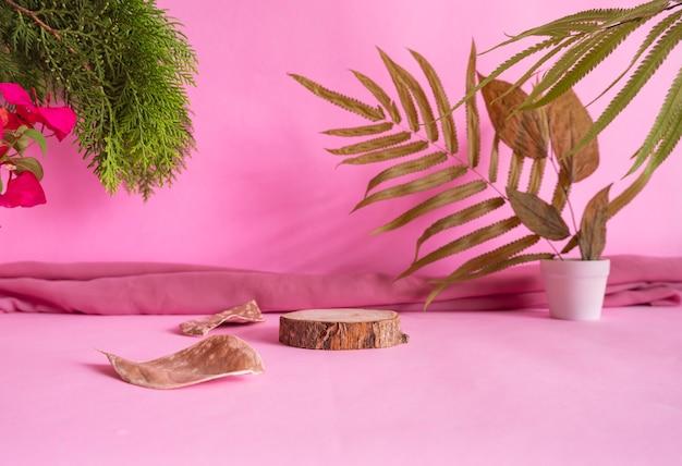 제품을 특징으로 하는 구성 아이디어 개념. 마른 잎, 녹색 잎, 천으로 장식된 분홍색 배경의 둥근 나무
