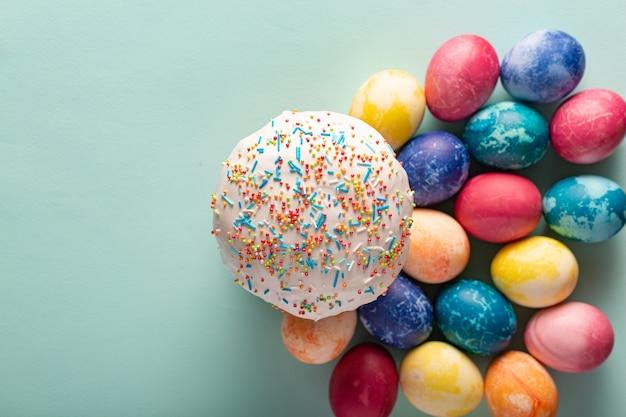 ミニマリズム風の作曲。ホリデーケーキとカラフルな卵、コピースペースとイースターの背景