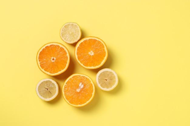 テキスト用のスペースを備えた黄色の背景に半分のレモンとオレンジのミニマリズムのスタイルの構成、上からの眺め
