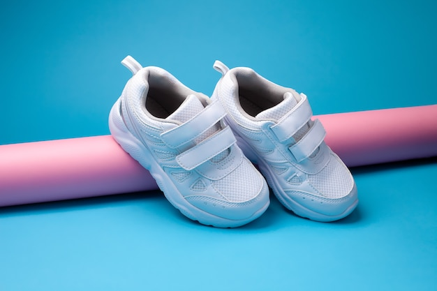 The composition is a balance of two white childrens sneakers with velcro fasteners for easy footwear...