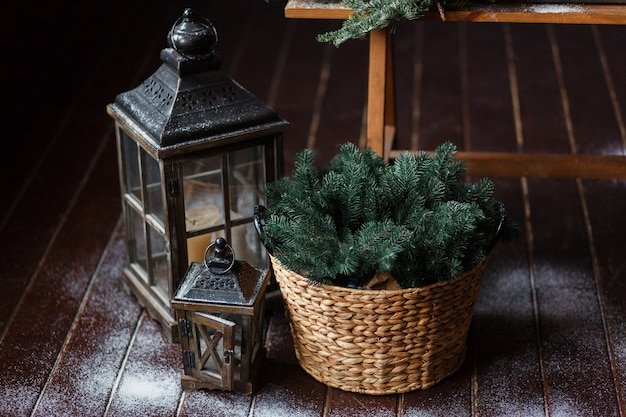 Composition of a lantern and fir branches on floor, decorated with snow