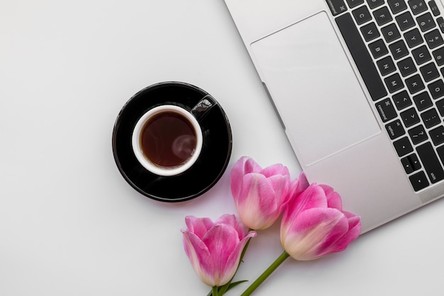 Composition of laptop with tulips and coffee cup