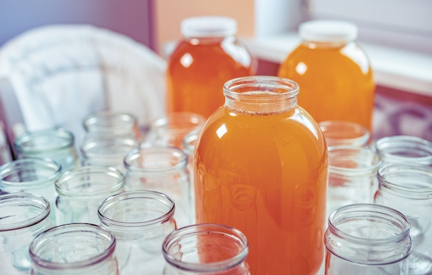 Composition of a large number of jars and three jars of honey standing on a white table against a background of light