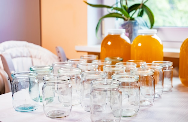 Composition of a large number of transparent empty glass jars and three large glass transparent jars with yellow sweet honey, standing on a large white table against a background of bright sunlight