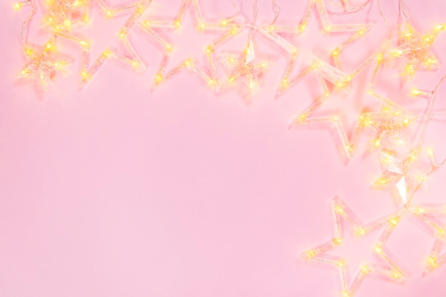 Composition light garland a on pink background. frame of garland star on pink background